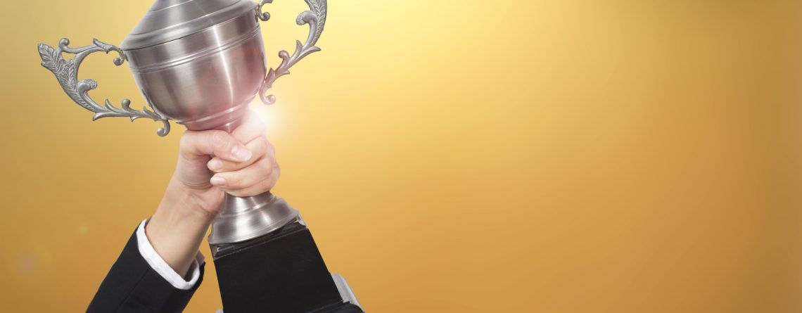 Businesswoman holding trophy award for success in business. gold background